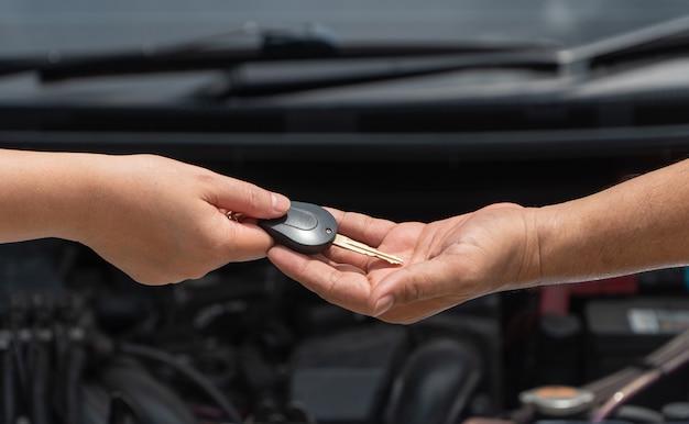 Schließen sie oben von der kundenhand, die dem automotorschlosser auf automotorhintergrund autoschlüssel gibt, um ihn zu reparieren.