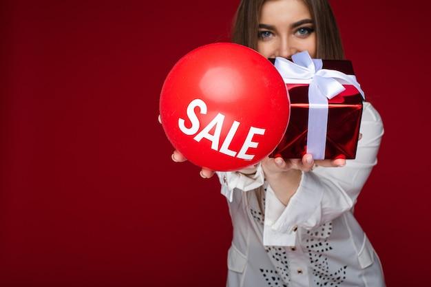 Schließen sie oben von der lächelnden frau, die roten ballon mit einem inschriftenverkauf zeigt