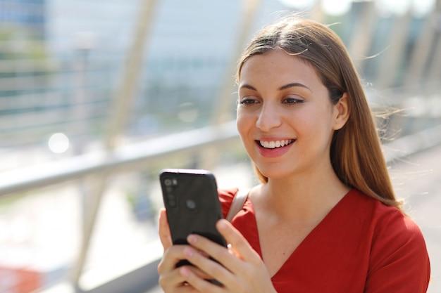 Schließen sie oben von der lächelnden geschäftsfrau, die einkaufs-online-app auf smartphone in der stadtstraße verwendet