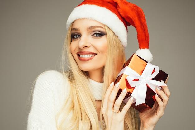 Schließen sie oben von der lächelnden schönen frau, die mit der roten geschenkbox für weihnachten aufwirft