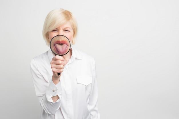 Schließen sie oben von der lustigen frau in der weißen bluse, die eine zunge durch die lupe zeigt.