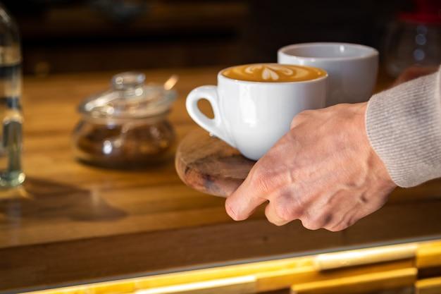 Schließen sie oben von der männlichen hand, die eine schale für heißen kaffee nimmt