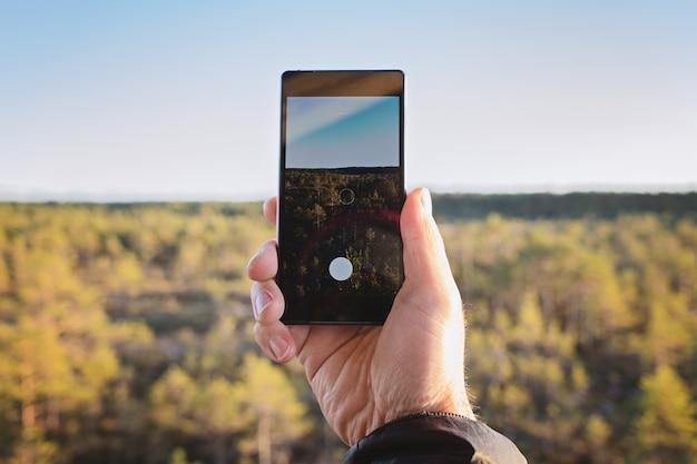 Schließen sie oben von der männlichen hand, die intelligentes telefon hält und foto macht