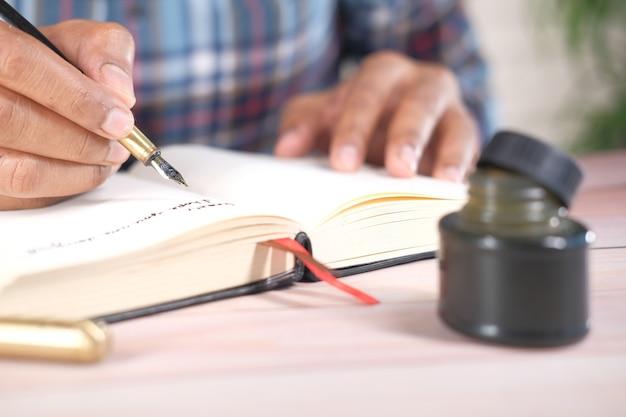 Schließen sie oben von der mannhand, die einen brief mit füllfederhalter schreibt