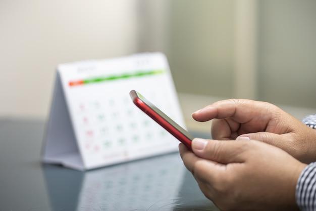 Schließen sie oben von der mannhand, die mobilen smartphone mit tischplattenkalender hält und verwendet.