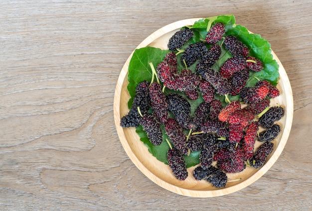 Schließen sie oben von der maulbeere mit blätter eines grüns auf der hölzernen platte auf holztisch.