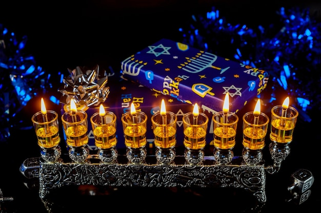 Schließen sie oben von der menora mit kerzen für chanukka und geschenkbox auf hintergrund. jüdischer feiertag.