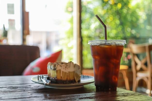Schließen sie oben von der mitnehmerplastikschale gefrorenem schwarzem kaffee (americano) mit stück banoffee auf holztischkuchentorte im restaurant