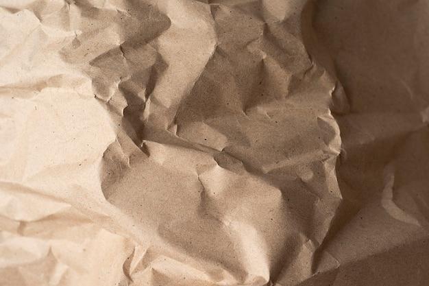 Schließen sie oben von der recycelten braunen faltenpapierstruktur für hintergrund oder design oder kunstwerk. draufsicht nahaufnahme papierhintergrund
