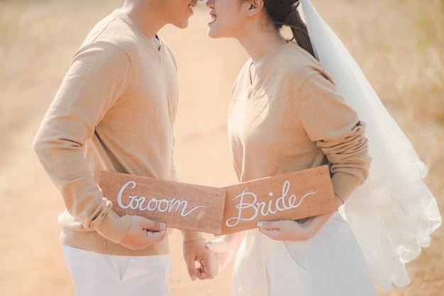 Schließen sie oben von der reizenden braut und vom bräutigam, die draußen hölzerne platte des zeichens hält. romantisches paar und liebeskonzept