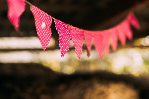 Schließen sie oben von der retro-girlande mit bunten roten fahnen mit weißen punkten bei sonnenuntergang im sommergarten. alles gute zum geburtstagsfeierkonzept. stoff urlaub dekorationen im freien.