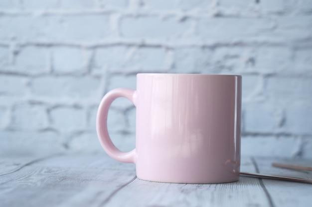 Schließen sie oben von der rosa farbe kaffeetasse auf dem tisch