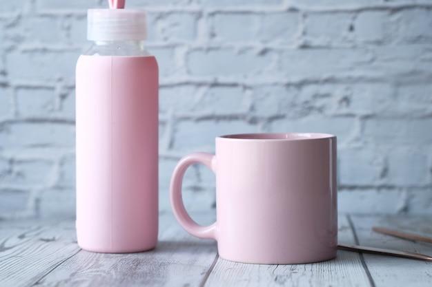 Schließen sie oben von der rosa farbe kaffeetasse und einer flasche auf dem tisch