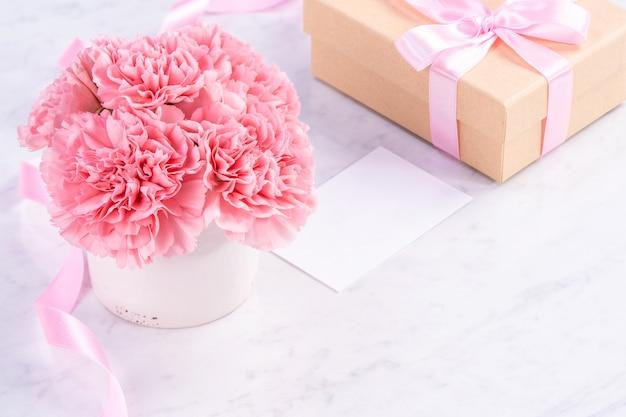 Schließen sie oben von der rosa nelke auf weißem marmorhintergrund für muttertagsblume