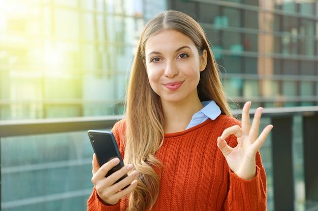 Schließen sie oben von der schönen frau, die das smartphone hält, das ok zeichen an der kamera tut