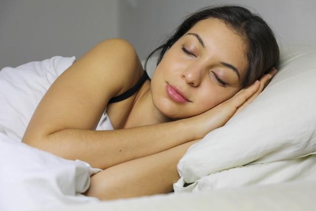 Schließen sie oben von der schönen jungen frau, die lächelt, während sie in ihrem bett zu hause schlafen