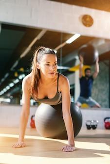 Schließen sie oben von der schönen kaukasischen frau mit pferdeschwanz und langen braunen haaren, die übungen mit pilatesball im fitnessstudio tun. in hintergrundreflexion des mannes mit pilatesball.
