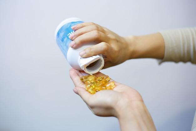 Schließen sie oben von der schönheit mit fischölkapseln von glas zu hand.