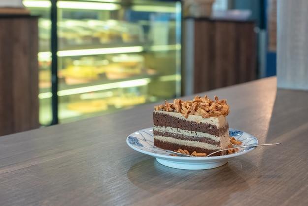 Schließen sie oben von der schokolade auf platte auf hölzernem schreibtisch in der kaffeestube
