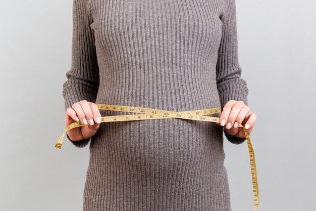 Schließen sie oben von der schwangeren frau im grauen kleid, das ihren wachsenden bauch am grauen hintergrund misst. ein kind erwarten. zollmessung.