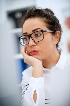 Schließen sie oben von der stilvollen professionellen geschäftsfrau, die gelangweilt am schreibtisch vor einem laptop sitzt.