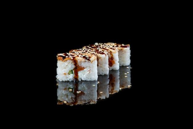 Schließen sie oben von der sushi-rolle auf einem schwarzen hintergrund japanisches gericht