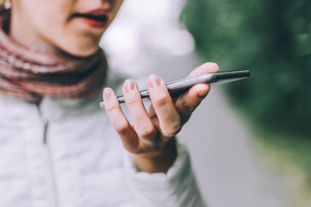 Schließen sie oben von der weiblichen hand, die smartphone hält. verwenden der sprachwahl zum eingeben von nachrichten.