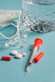 Schließen sie oben von diabetes-spritze mit pillen und glasfläschchen auf blauem hintergrund. gesundheitskonzept