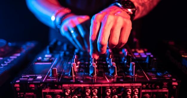 Schließen sie oben von dj-händen, die eine musiktabelle in einem nachtclub steuern.