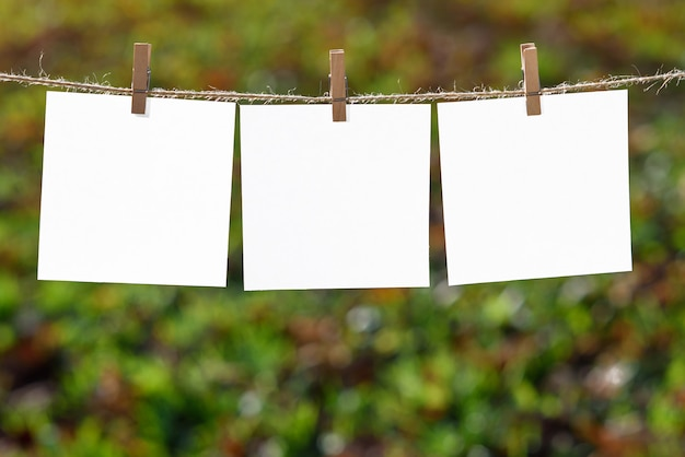 Schließen sie oben von drei weißen briefpapieren, die durch hölzerne wäscheklammern gehangen werden
