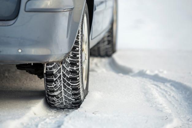 Schließen sie oben von einem autoreifen, der am wintertag auf verschneiter straße geparkt wird. transport- und sicherheitskonzept.