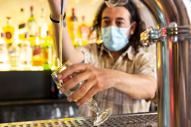 Schließen sie oben von einem barmann, der eine medizinische maske trägt, die ein bierglas in einer modernen bar füllt.