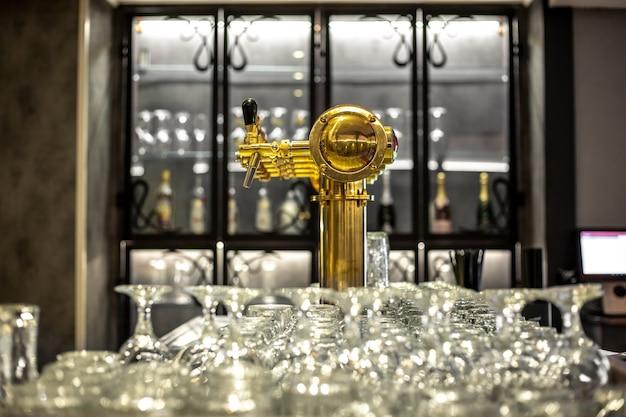 Schließen sie oben von einem bierhahn oder zapfhahn mit der riesigen ansammlung einer leeren gläser in der bar oder im pub, restaurantkonzept