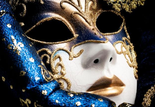 Schließen sie oben von einem blau mit goldeleganter traditioneller venetianischer maske über weißem hintergrund