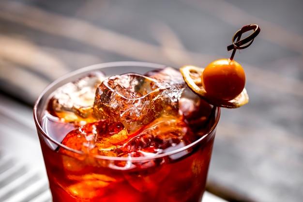 Schließen sie oben von einem cocktailglas mit eiswürfeln, die mit getrockneter zitrone und früchten garniert werden