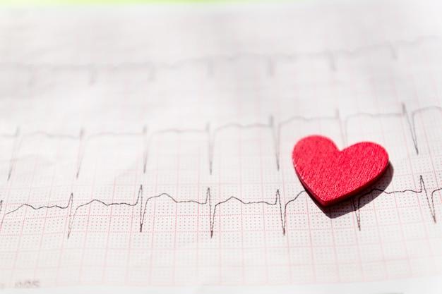 Schließen sie oben von einem elektrokardiogramm in der papierform vith rotes hölzernes herz. ecg- oder ekg-papierhintergrundbeschaffenheit. medizin- und gesundheitskonzept.