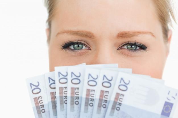 Schließen sie oben von einem frauengesicht, das mit eurobanknoten versteckt wird