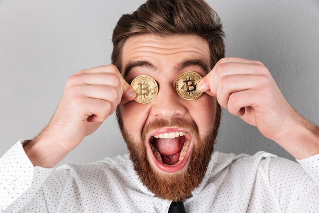 Schließen sie oben von einem frohen geschäftsmann mit bitcoins in seinen augen