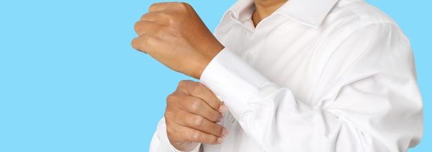 Schließen sie oben von einem geschäftsmann, der auf dem ärmel seines weißen hemdes mit dem kopienraum lokalisiert auf blauem hintergrund knöpft. beschneidungspfade.