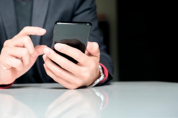 Schließen sie oben von einem geschäftsmann, der intelligentes mobiltelefon beim sitzen im büro verwendet