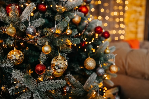 Schließen sie oben von einem geschmückten weihnachtsbaum mit roten und goldenen kugeln