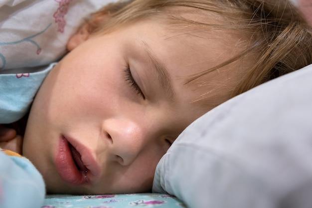 Schließen sie oben von einem gesicht des hübschen kleinen kindermädchens mit leicht geöffnetem mund und verstreut um haare, die zu hause im bett schlafen.