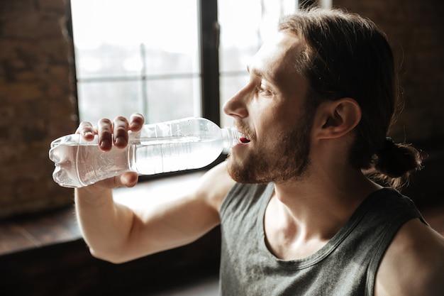 Schließen sie oben von einem gesunden jungen fitnessmann, der wasser trinkt