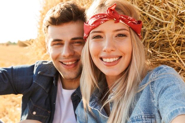 Schließen sie oben von einem glücklichen jungen paar, das am weizenfeld sitzt