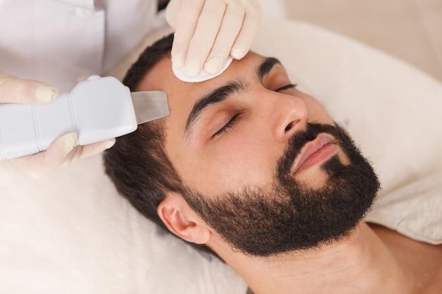 Schließen sie oben von einem gutaussehenden bärtigen mann, der ultraschallreinigung durch kosmetikerin erhält