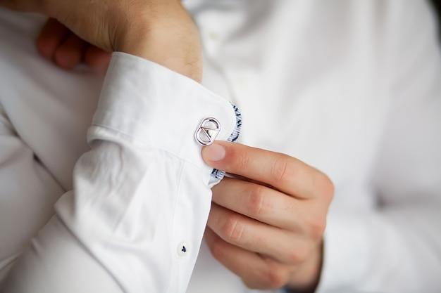 Schließen sie oben von einem handmann, wie weißes hemd und manschettenknopf trägt