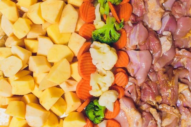 Schließen sie oben von einem hausgemachten huhn, das mit kartoffeln und brokkoli gegrillt wird.