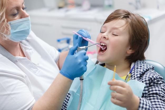 Schließen sie oben von einem jungen, der fluorid-zahnbehandlung durch seinen zahnarzt erhält