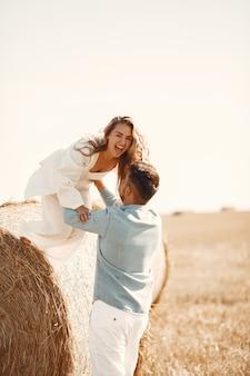 Schließen sie oben von einem jungen paar, das am weizenfeld sitzt. die leute sitzen auf dem heuhaufen auf der wiese und umarmen sich.