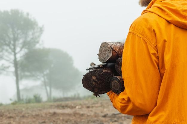 Schließen sie oben von einem kaukasischen mann, der brennholzprotokolle in einem nebligen wald hält, der orange regenmantel während eines regnerischen tages trägt